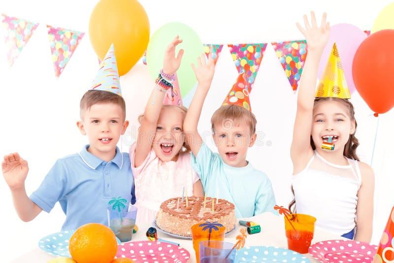 De gelukkige kinderen die met verjaardag stellen koeken royalty-vrije stock foto's