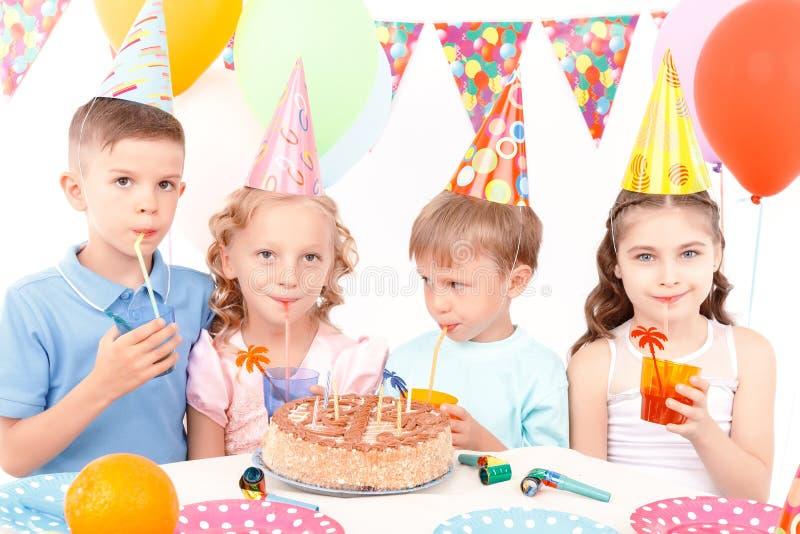 De gelukkige kinderen die met verjaardag stellen koeken stock fotografie