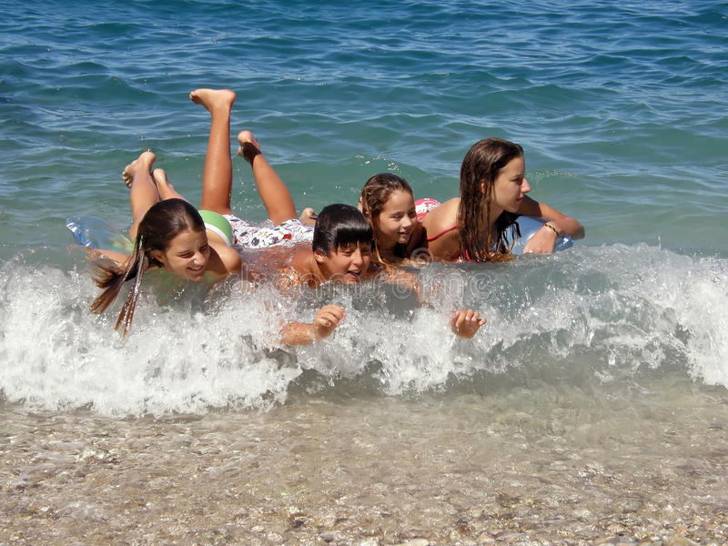 De gelukkige kinderen genieten van op golven royalty-vrije stock afbeelding