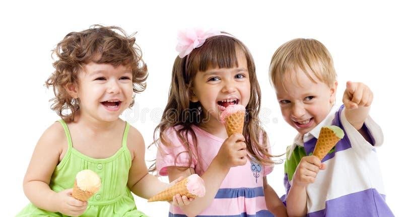 De gelukkige kinderen groeperen zich met roomijs in studio stock afbeelding