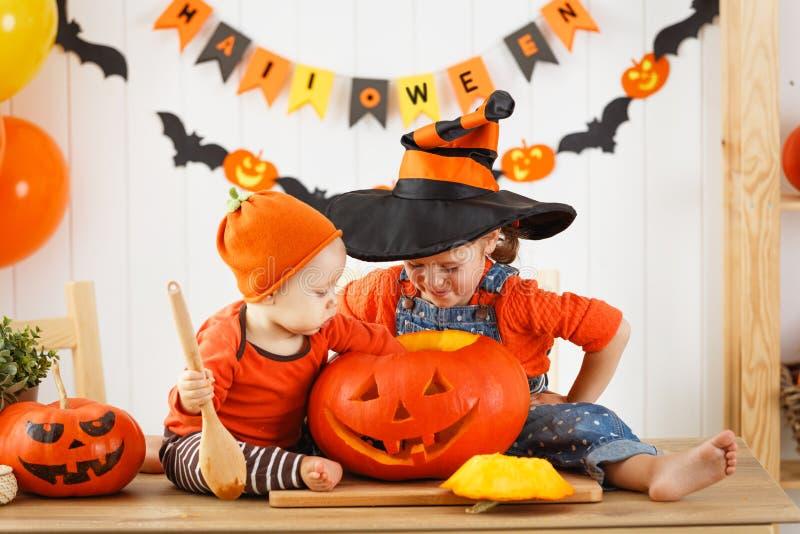 De gelukkige kinderen snijden een pompoen voor Halloween stock fotografie