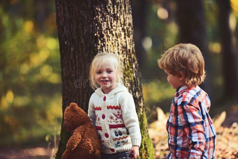 De gelukkige kinderen spelen in de herfst bos Gelukkige familie, vriendschap, liefde en vertrouwen royalty-vrije stock foto's