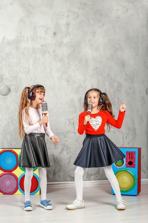 Download De Gelukkige Kinderen Zingen En Luisteren Aan Muziek In Hoofdtelefoons Conce Stock Foto - Afbeelding bestaande uit meisje, leisure: 107704036