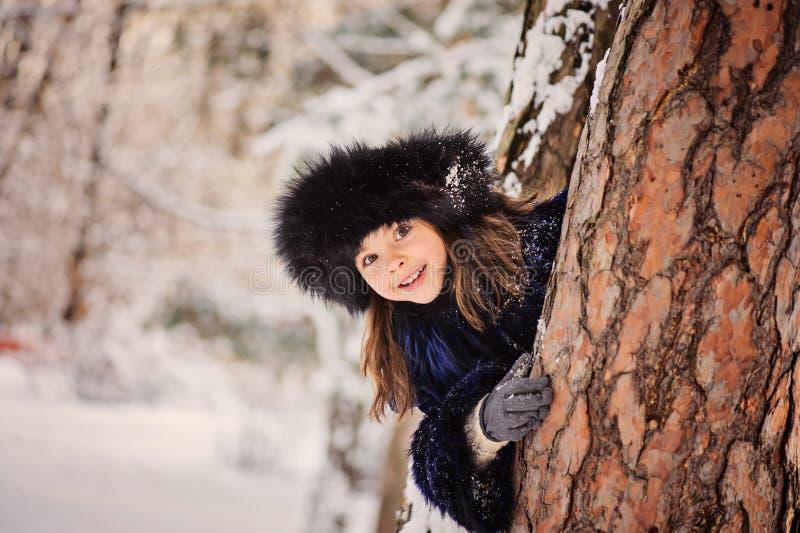De gelukkige kindmeisje het spelen huid - en - zoekt in de winterbos royalty-vrije stock fotografie