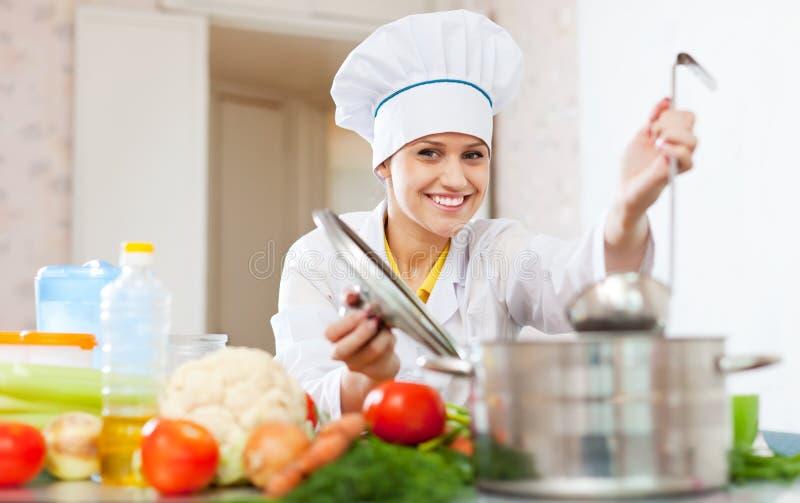 De gelukkige kok in witte eenvormig bereidt lunch voor stock afbeelding