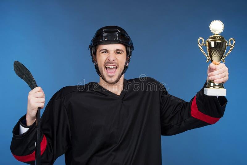 De gelukkige kop van de winnaarholding. stock foto