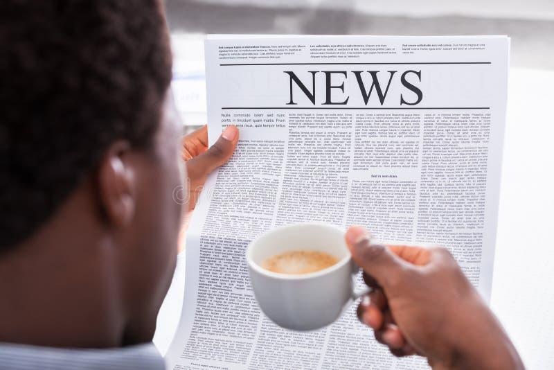 De gelukkige krant van de zakenmanlezing stock foto's