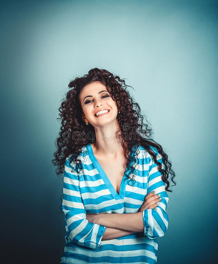 De gelukkige krullende vrouw bewapent het gekruiste glimlachen stock foto