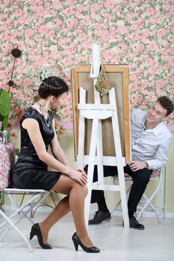 De gelukkige kunstenaar gluurt uit van achter zijn schildersezel op mooie vrouw stock fotografie