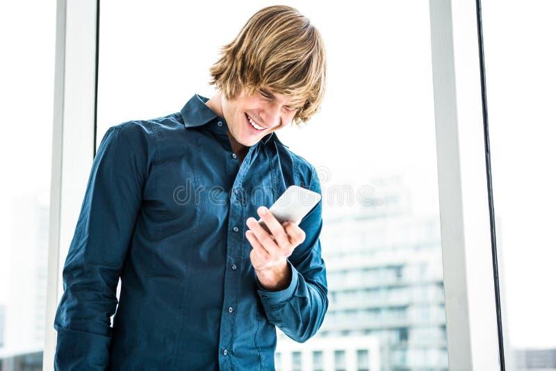 De gelukkige lach die van de hipsterzakenman zijn telefoon bekijken royalty-vrije stock foto