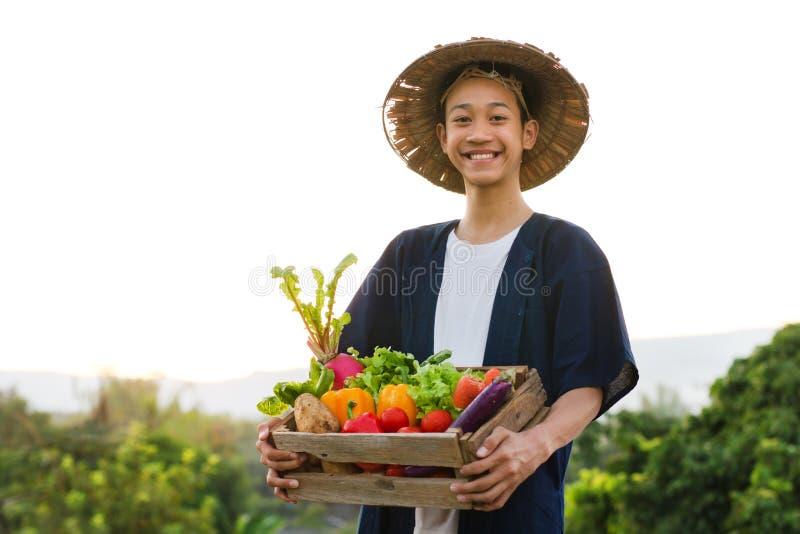 De gelukkige landbouwer die van Azië terwijl greep divers van plantaardig product glimlachen royalty-vrije stock afbeelding