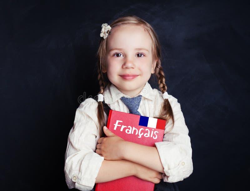 De gelukkige leerling van het kindmeisje met Frans studieboek stock fotografie