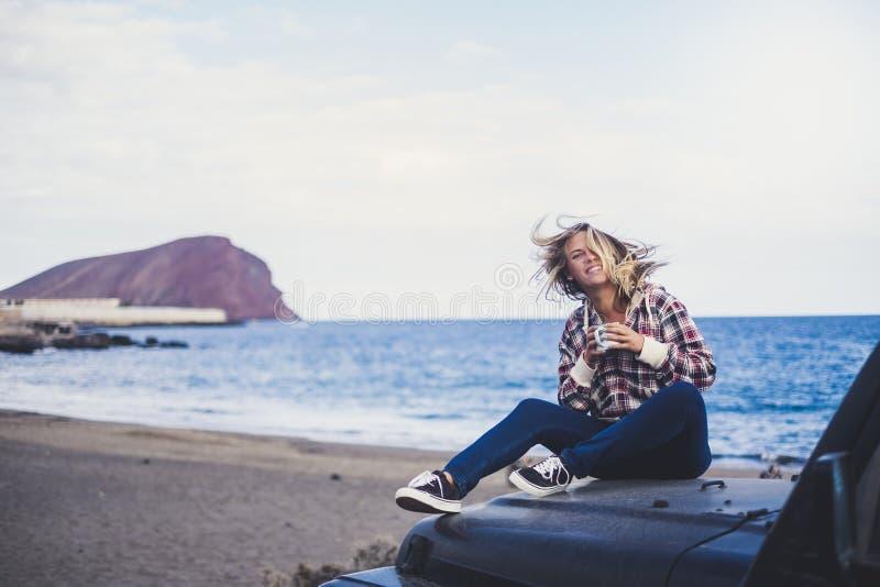 De gelukkige leuke zitting van het blonde jonge meisje op de neus van haar avonturenauto die van de wind en van de de zomer alter stock fotografie