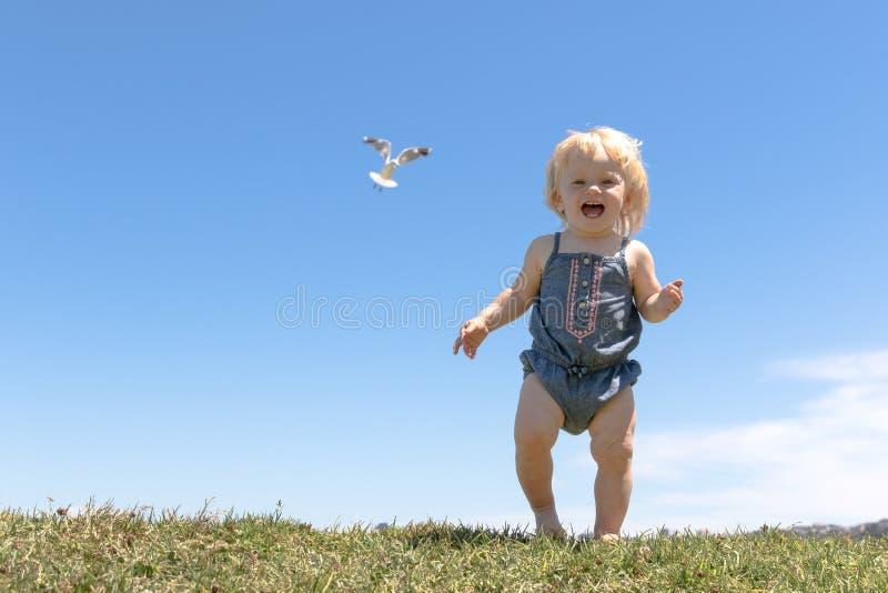 De gelukkige looppas van het babymeisje bovenop de heuvel royalty-vrije stock afbeeldingen