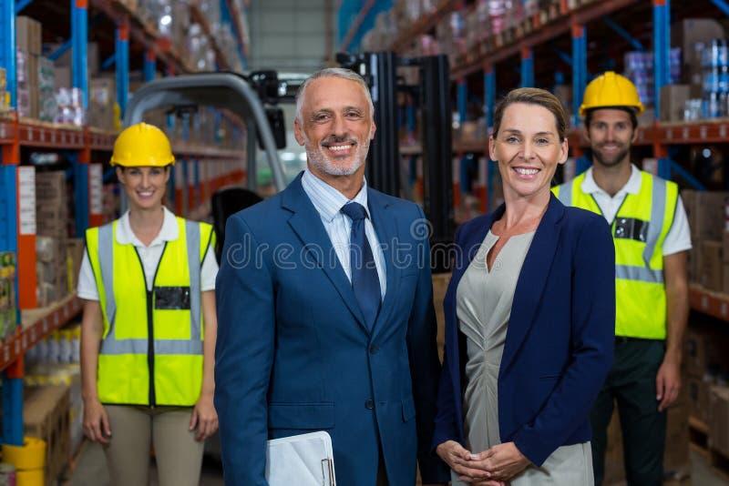 De gelukkige managers stellen voor de arbeiders royalty-vrije stock afbeeldingen