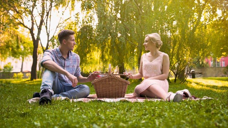 De gelukkige mand van de paar uitpakkende picknick, die van prachtige rust in park samen genieten stock afbeeldingen