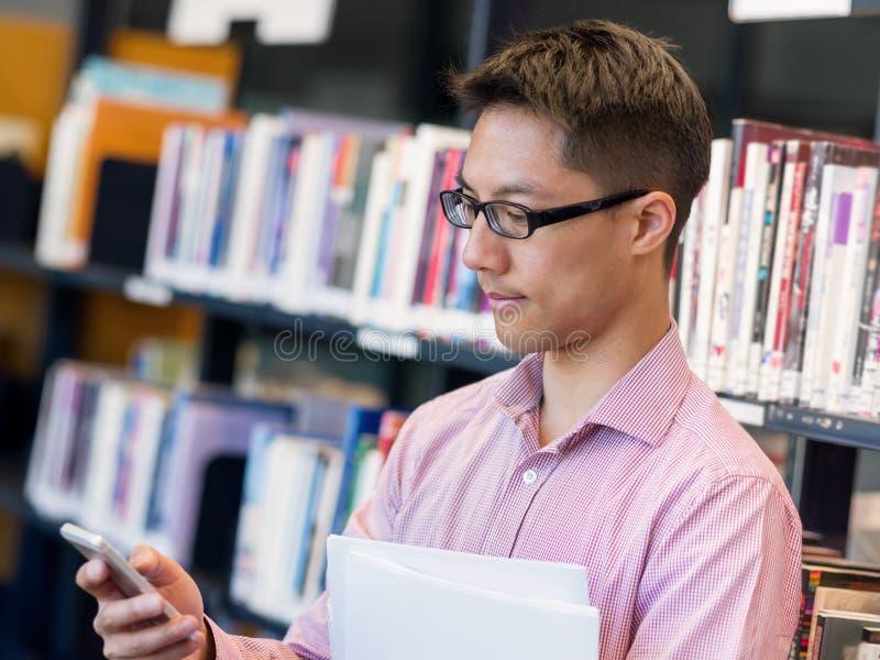 De gelukkige mannelijke boeken van de studentenholding bij de bibliotheek stock afbeeldingen