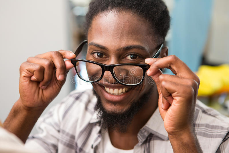 De gelukkige mannelijke glazen van het de holdingsoog van de manierontwerper stock foto