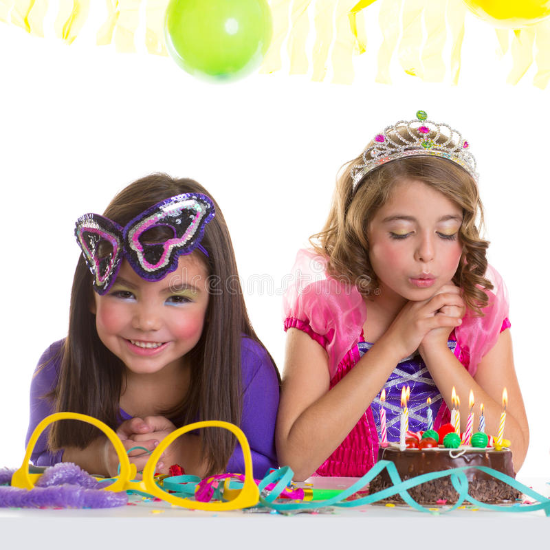 De gelukkige meisjes die van kinderen de cake van de verjaardagspartij blazen royalty-vrije stock afbeeldingen
