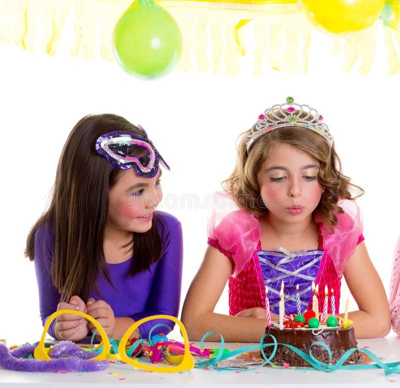 De gelukkige meisjes die van kinderen de cake van de verjaardagspartij blazen royalty-vrije stock afbeelding