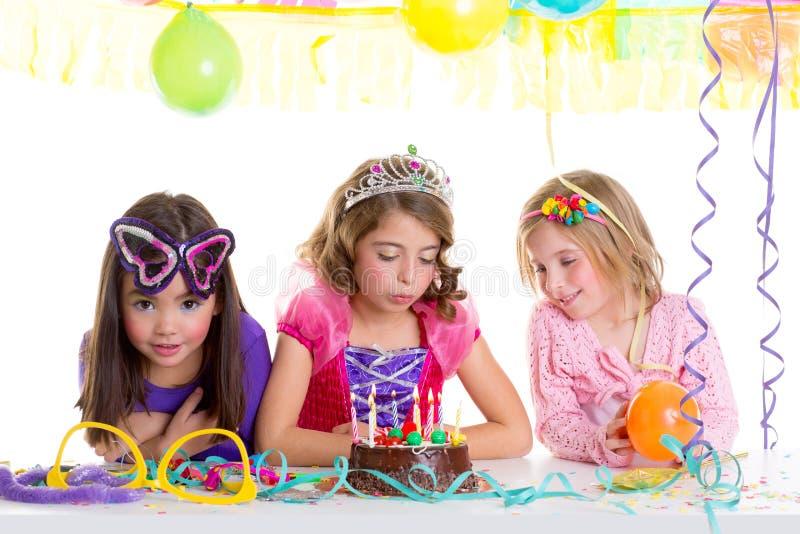 De gelukkige meisjes die van kinderen de cake van de verjaardagspartij blazen stock foto