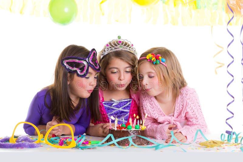 De gelukkige meisjes die van kinderen de cake van de verjaardagspartij blazen stock afbeeldingen