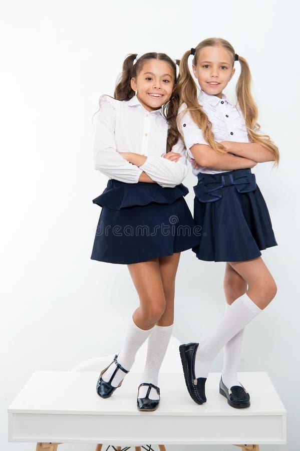 De gelukkige meisjes glimlachen in eenvormige school Terug naar School De mooie kledings kleine krullen, danken hemel voor meisje royalty-vrije stock afbeelding