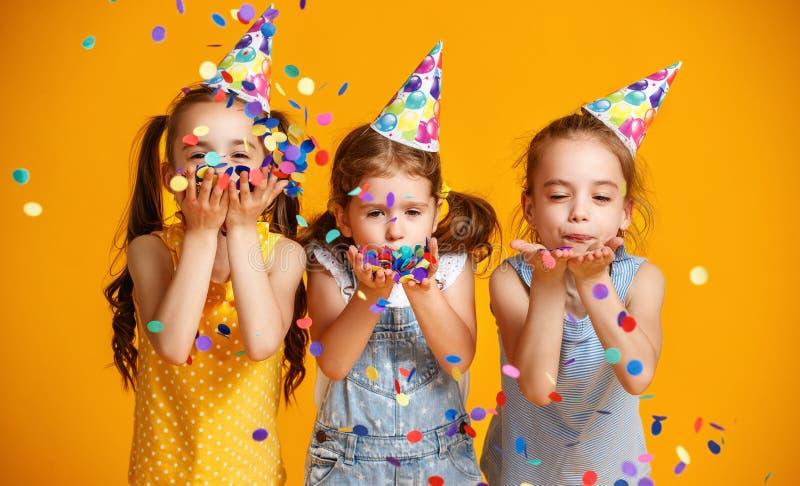 De gelukkige meisjes van verjaardagskinderen met confettien op gele achtergrond stock foto
