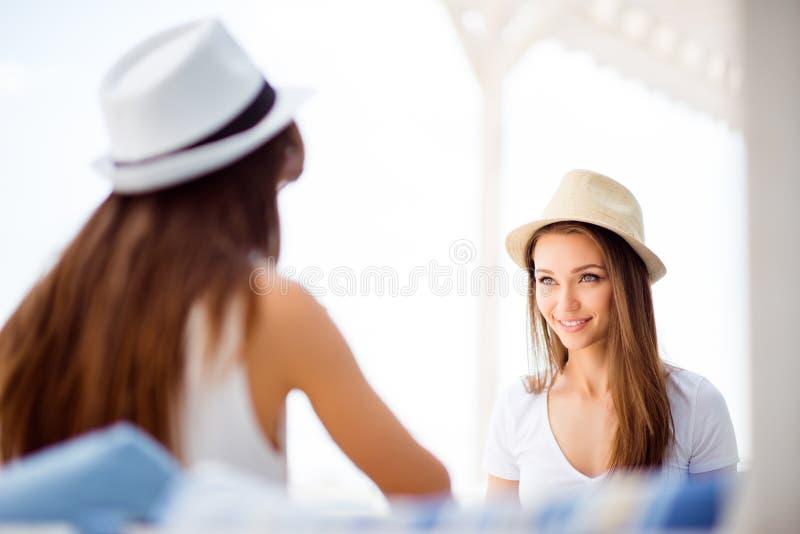 De gelukkige meisjes zitten in de zomer buiten openluchtlig royalty-vrije stock afbeeldingen