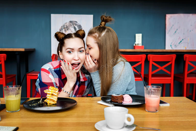 De gelukkige meisjesvrienden hebben kop van koffie in modern stadsrestaurant stock fotografie