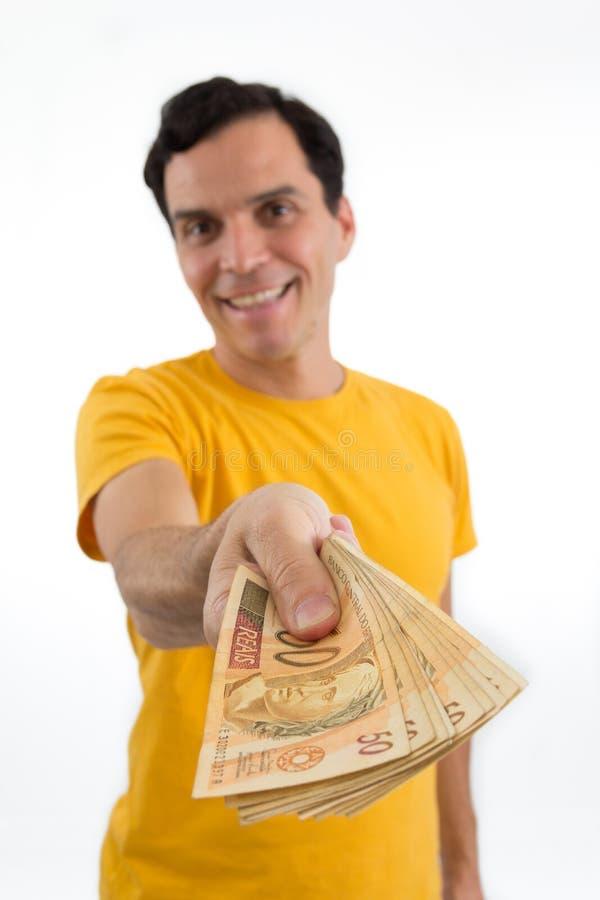 De gelukkige mens deelt geld uit Hij ` s op zijn voeten Geïsoleerd op wh royalty-vrije stock afbeelding