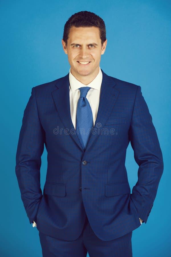 De gelukkige mens die glimlachen met dient zakken in elegant kostuum in stock fotografie