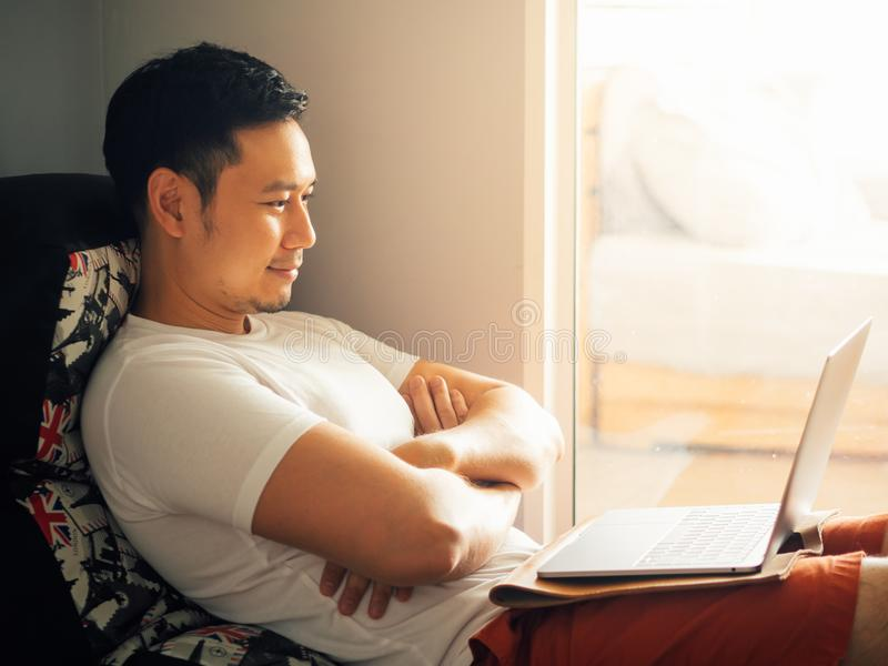 De gelukkige mens gebruikt laptop en ontspant op bank in de ochtend stock foto