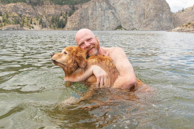 De gelukkige mens houdt zijn golden retrieverhond terwijl het zwemmen in het water stock afbeeldingen