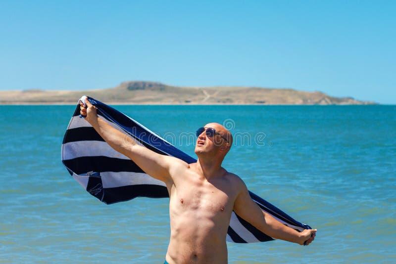 De gelukkige mens op het strand geniet van de vrijheid van het concept rust en vakantie stock afbeeldingen