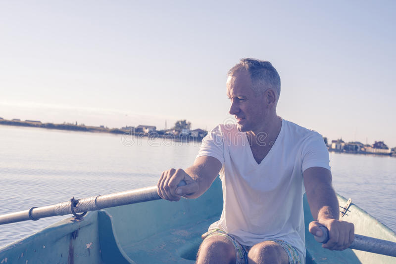 De gelukkige mens roeit op een kleine boot en het dromen royalty-vrije stock afbeelding