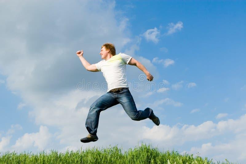 De gelukkige mens springt stock foto's