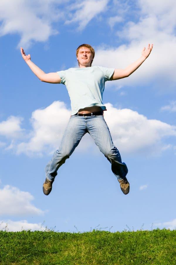 De gelukkige mens springt stock foto
