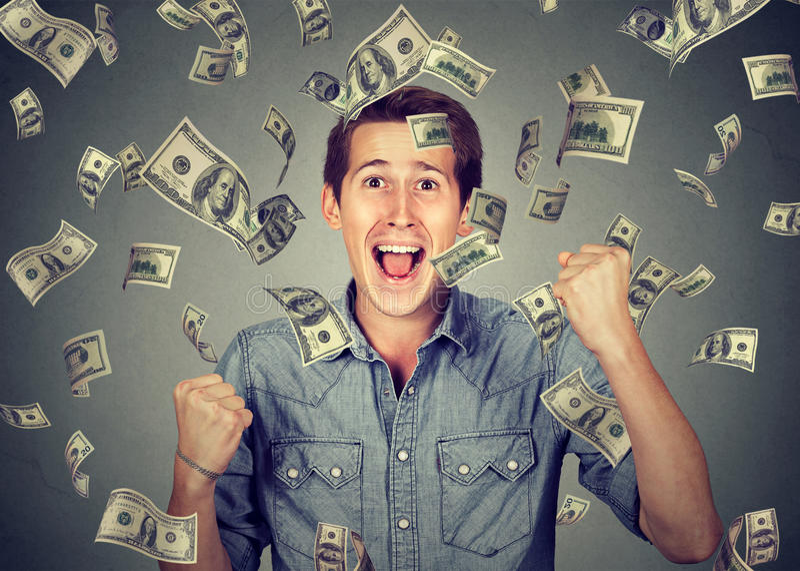 De gelukkige mens viert succes onder geldregen stock foto