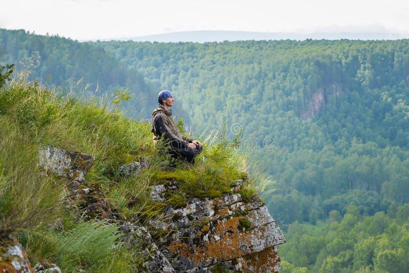 De gelukkige mens zit op de rand van een klip boven het bos, vrije tijd in harmonie met aard stock foto's