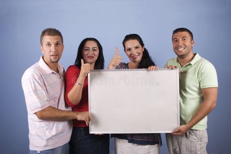 De gelukkige mensen met banner geven duimen op stock fotografie