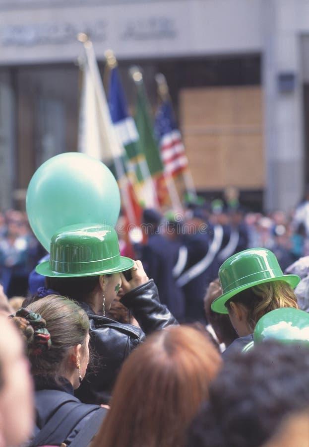De gelukkige mensen met groene bowlingspelerhoeden en de ballons die bij St Patrick's Dag toejuichen paraderen in de straten royalty-vrije stock fotografie