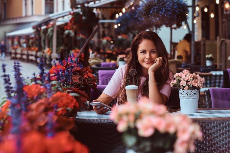 De gelukkige middenleeftijdsonderneemster met lang bruin haar die een roze kleding dragen houdt smartphone terwijl het zitten bij stock fotografie