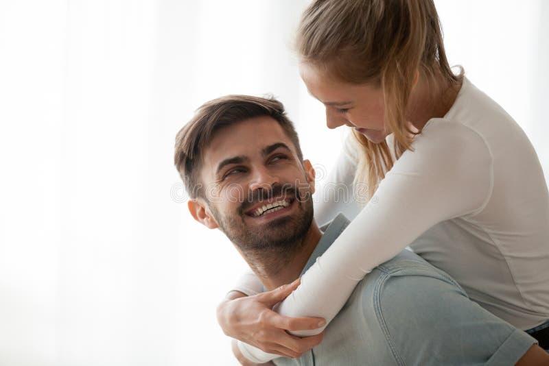 De gelukkige millennial glimlachende echtgenoot die van het vrouwenvervoer per kangoeroewagen pret hebben bij ho stock afbeelding