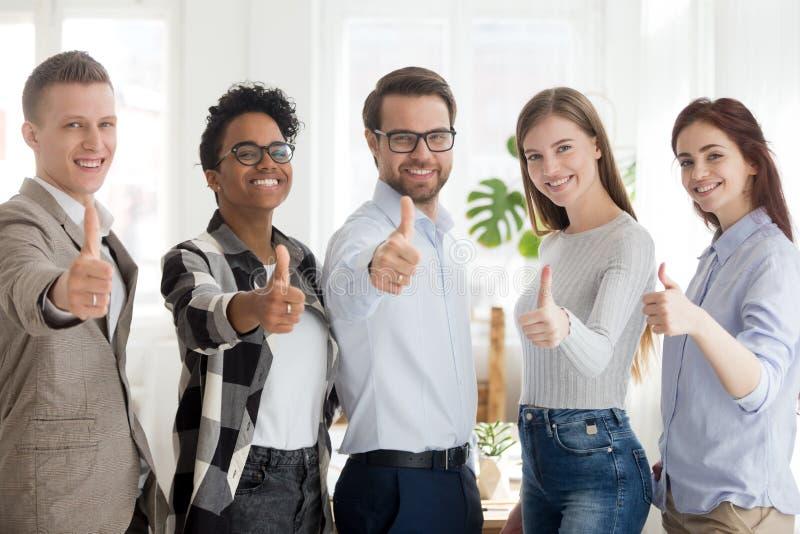 De gelukkige millennial mensen die het tonen bevinden zich beduimelen omhoog stock fotografie