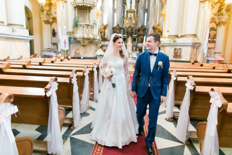 De gelukkige modieuze jonggehuwden die holding lopen dient de kerk op huwelijksceremonie in stock foto's