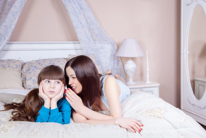 De gelukkige moeder en de dochter lagen in bed die pret, moeder het vertellen geheim aan haar dochter hebben stock afbeelding