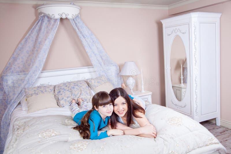 De gelukkige moeder en de dochter lagen in bed en het hebben van pret stock fotografie
