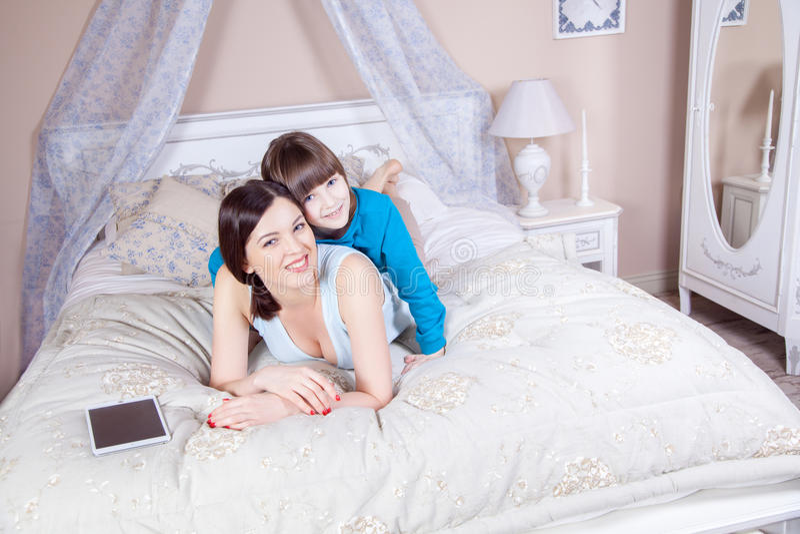 De gelukkige moeder en de dochter lagen in bed met digitale tablet die, die en camera glimlachen bekijken royalty-vrije stock afbeelding