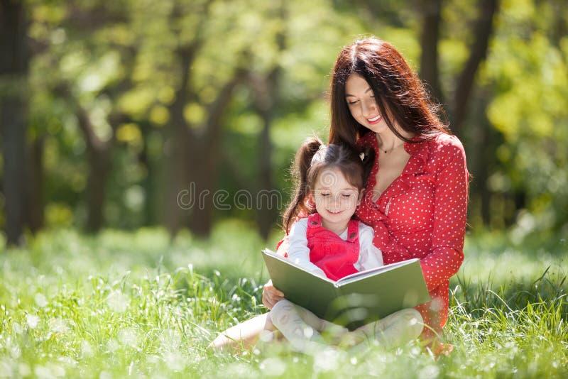 De gelukkige moeder en de dochter lezen een boek in de zomerpark De sc?ne van de schoonheidsaard met familie openluchtlevensstijl stock foto's